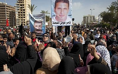 Egyptian protesters chant anti-President Mohammed Morsi slogans and carry posters with pictures of victims of recent violence in Port Said, Egypt, on Friday (photo credit: AP/Nasser Nasser)