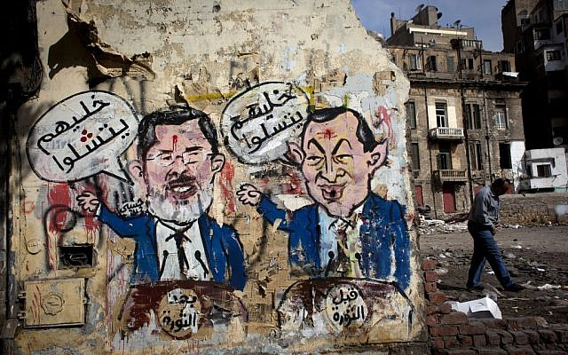An Egyptian man walks by a mural depicting ousted president Hosni Mubarak, right, and Egyptian President Mohammed Morsi, left, with Arabic that reads 'Before the revolution, let them be amused, after the revolution, let them be paralyzed,' on a wall in Tahrir Square, Cairo, Egypt, Tuesday, Feb. 19, 2013 (photo credit: AP/Nasser Nasser)