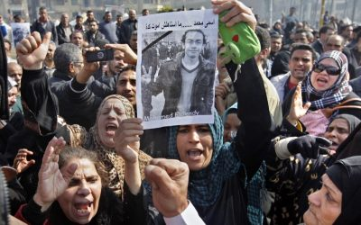Egyptian relatives of Mohammed el-Gindy, a 28-year-old activist, who died early Monday of wounds sustained during clashes last Friday near the presidential palace, display his picture as they shout anti-president Morsi slogans during his funeral procession in Tahrir Square, Cairo, Egypt, Monday, Feb. 4 (photo credit: AP/Amr Nabil)