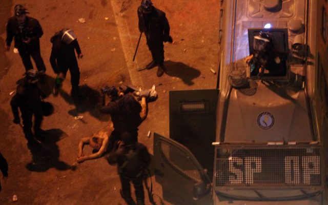 Egyptian riot police beat a man, after stripping him, and before dragging him into a police van, during clashes next to the presidential palace in Cairo, Egypt, on Friday, Feb. 1, 2013. (photo credit: AP/Khalil Hamra)