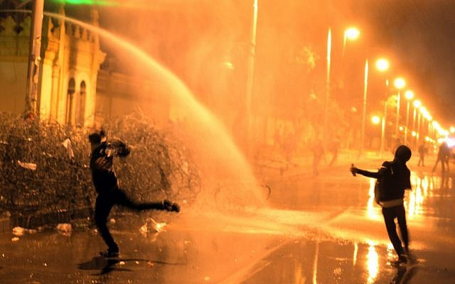 Egyptian protesters throw stones while security police fire water cannon in Cairo, Egypt, Monday, Feb. 11, 2013. (photo credit: AP/Khalil Hamra)