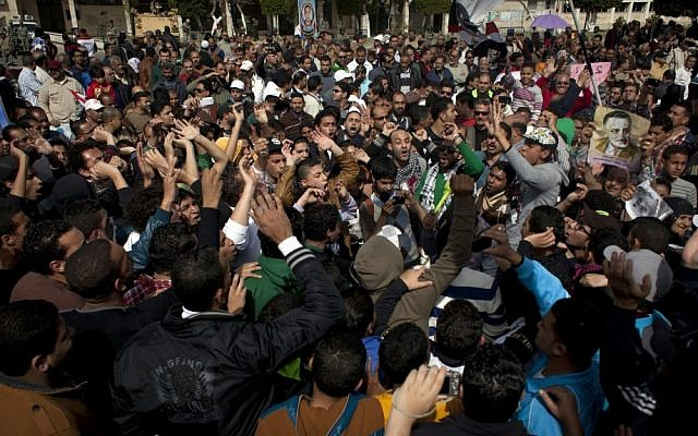 Hard-core soccer fans chant anti-president Mohammed Morsi slogans while attending a rally in front of the provincial government headquarters in Port Said, Egypt on Friday (photo credit: AP/Nasser Nasser)