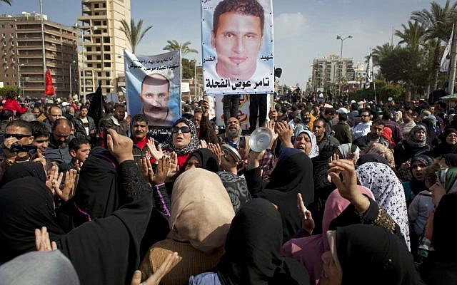 Egyptian protesters chant anti-Morsi slogans and carry posters with pictures of victims of recent violence and their names in Port Said, Egypt, February 22, 2013. (photo credit: AP/Nasser Nasser)