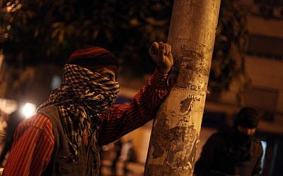 An Egyptian protester covers his face as he stands during clashes with riot police, not seen, near the presidential palace in Cairo, Egypt, Monday, Feb. 11, 2013. (photo credit: AP/Khalil Hamra)