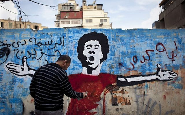 An Egyptian activist paints a mural depicting a slain activist with Arabic that reads 'Why did you do this? This is very sad,' on a wall in Tahrir Square in Cairo, Egypt, on February 19, 2013. (photo credit: Nasser Nasser/AP)