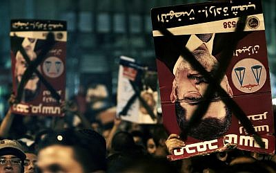 Egyptians chant slogans and hold defaced posters with the photo of President Mohammed Morsi in Tahrir Square, Cairo, May 2012 (photo credit: Fredrik Persson/AP)