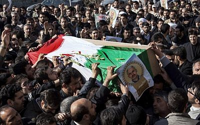 Iranian mourners carry the flag draped coffin of Gen. Hassan Shateri, shown in the poster, in Tehran. Prominent Iranian politicians and clerics led mourners at a funeral Thursday for a senior commander of the country's powerful Revolutionary Guards who was killed this week while traveling from Syria to Lebanon, local media said. (AP Photo/Fars News Agency, Saeed Kariminejad