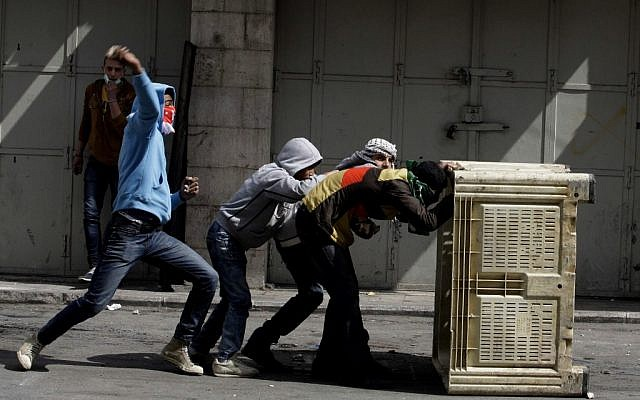 Palestinians take cover during clashes with Israeli troops in the West Bank city of Hebron on Sunday. (photo credit: AP/Nasser Shiyoukhi)