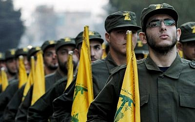 Hezbollah fighters hold party flags during a parade in a southern suburb of Beirut, Lebanon (AP/Hussein Malla/File)