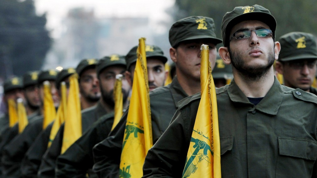 Hezbollah fighters hold party flags as they parade during the opening of a new cemetery for colleagues who died in fighting against Israel, in a southern suburb of Beirut, Lebanon, November 2010 (photo credit: AP/Hussein Malla)