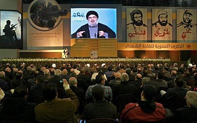 Hezbollah leader Sheik Hassan Nasrallah speaks via a video link during a ceremony to mark the anniversary of the death of Hezbollah leaders, in the southern suburbs of Beirut, Lebanon, Saturday, Feb. 16, 2013 (photo credit: AP/Bilal Hussein)