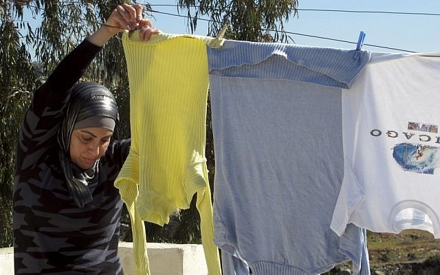 "Suraia Burnat, 42, wife of the Palestinian co-director of ""Five Broken Cameras"" hangs washing on the rooftop of their home in the West Bank village of Bilin last Sunday. (photo credit: AP/Diaa Hadid)"