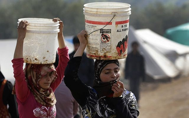 In this Tuesday, Feb. 19, 2013 photo, Syrian refugee girls carry over their heads buckets of water as they walk at Atmeh refugee camp, in the northern Syrian province of Idlib, Syria (photo credit: Hussein Malla/AP)
