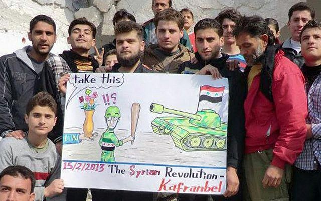 Anti-regime protesters hold a caricature placard during a demonstration in Idlib province, Syria, on Friday (photo credit: AP/Edlib News Network ENN)