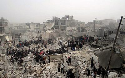 People searching through the debris of destroyed buildings in the aftermath of a strike by Syrian government forces, in the neighborhood of Jabal Bedro, Aleppo, Syria, February 19 (photo credit: AP/Aleppo Media Center AMC)