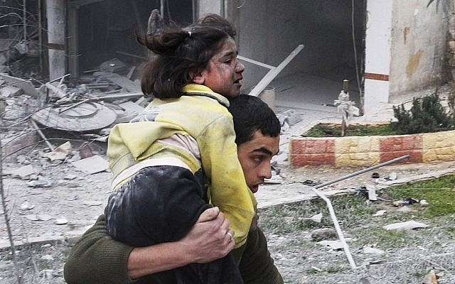 Syrian man carries his sister, who was wounded in a government airstrike, in Aleppo, Syria, on Sunday, February 3, 2013. (photo credit: AP Photo/Abdullah al-Yassin)