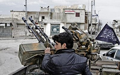 A Free Syrian Army fighter sits behind an anti-aircraft weapon in Aleppo, Syria (photo credit: AP/Abdullah al-Yassin)