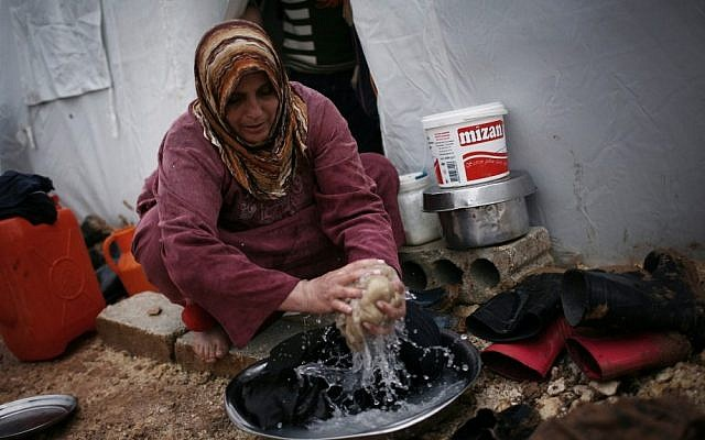 A displaced Syrian woman washes some clothes in front of her tent in the Azaz camp for displaced people, north of Aleppo province, Syria, Monday, Feb. 18, 2013 (photo credit: AP/Manu Brabo)