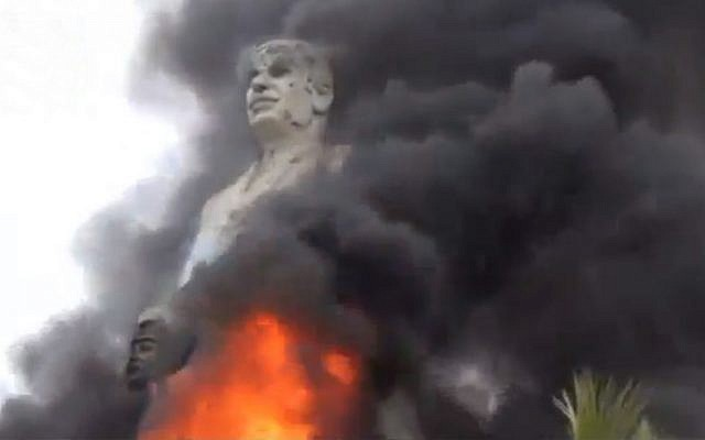 A statue of Hafez Assad, father of Syrian President Bashar Assad, burns after being set on fire by rebel fighters inside the grounds of the General Company of the Euphrates Dam in al-Raqqa, Syria, on Monday, February 11, 2013. (AP Photo/Ugarit News via AP video)
