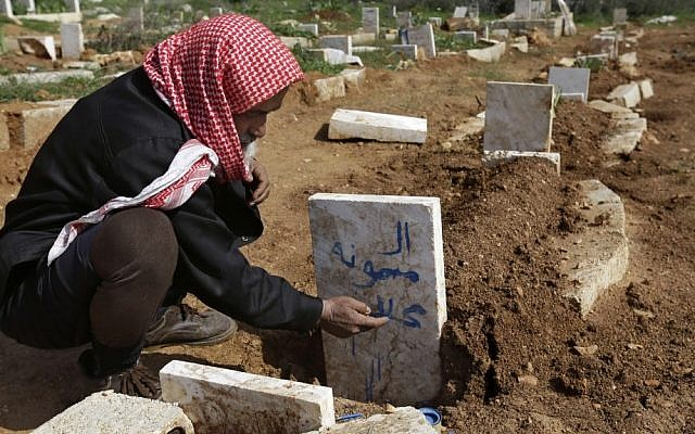 An illustrative photo of a Syrian villager writing the name of his granddaughter (who was killed by an airstrike by Syrian government forces) on her grave near the village of Sarja, in Idlib, Syria, on Sunday. (photo credit: AP/Hussein Malla)