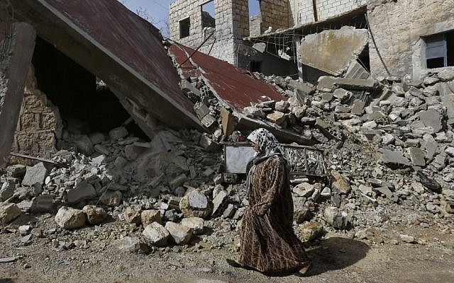 Illustrative photo of a Syrian woman walking past a house destroyed by a government airstrike in Idlib, Syria, on February 25, 2013. (photo credit: AP/Hussein Malla)