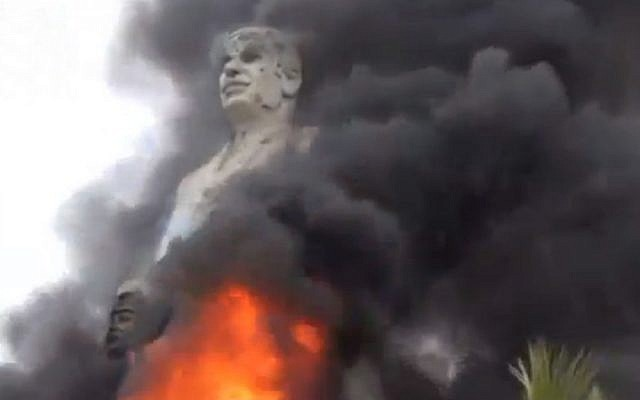 A statue of Hafez Assad, father of Syrian President Bashar Assad, burns after being set on fire by rebel fighters inside the grounds of the General Company of the Euphrates Dam in Al-Raqqa, Syria, Monday, Feb. 11 (photo credit: AP/Ugarit News)