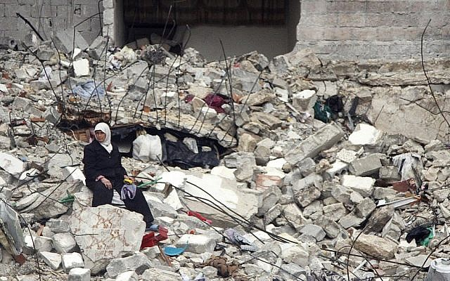 A Syrian woman sits on the ruins of her house, which was destroyed in a recent government airstrike that killed 11 members of her family, in Aleppo, Syria, on Thursday (photo credit: AP/Abdullah al-Yassin)