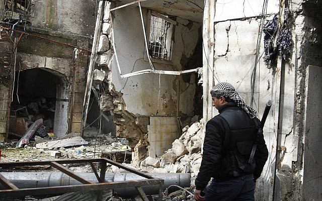 A Free Syrian Army fighter walks past destroyed shops in Aleppo, Syria, on Friday, February 8, 2013. (photo credit: AP/Abdullah Al-Yassin)