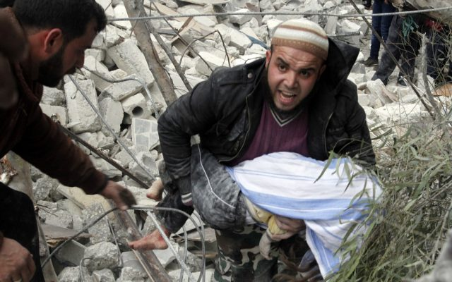 A Syrian man carries a child's body after a government airstrike hit the neighborhood of Ansari, in Aleppo, Syria on Sunday, February 3, 2013. (AP Photo/Abdullah al-Yassin)