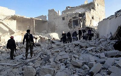 Syrian rebels stand in the rubble of damaged buildings due to government airstrikes, in the neighborhood of Karam Tarab near Aleppo International Airport, in Aleppo, Syria, Wednesday, February 13, 2013. (photo credit: AP/Aleppo Media Center AMC)