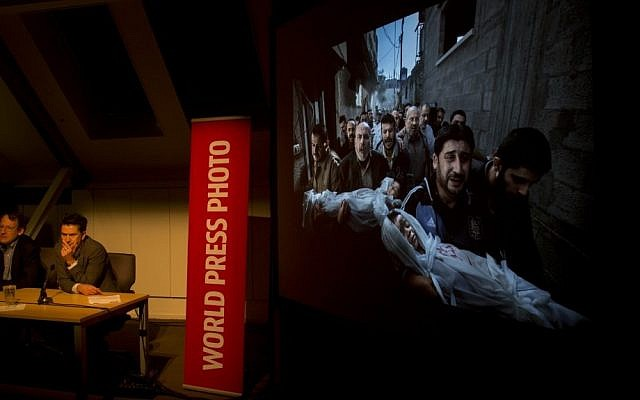 Members of the jury of the World Press Photo contest listen to questions during a press conference as the winning picture by Paul Hansen, Sweden, for Dagens Nyheter, is projected on a screen in Amsterdam in February. (photo credit: AP/Peter Dejong)