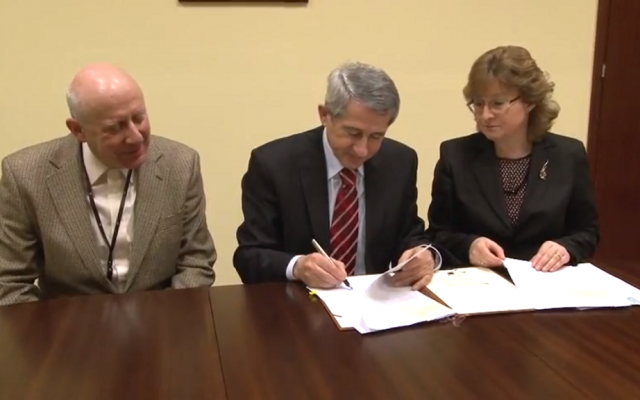 Polish State Archives general director Władysław Stępniak signs Friday's agreement at a ceremony attended by PSA official Ania Krochmal and Jewish Records Indexing representative Krzysztof Malczewsk. (YouTube screenshot)
