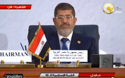 A visibly unamused Egyptian President Mohammed Morsi at Wednesday's meeting of the Organization of Islamic Cooperation summit in Cairo (photo credit: screen capture YouTube)