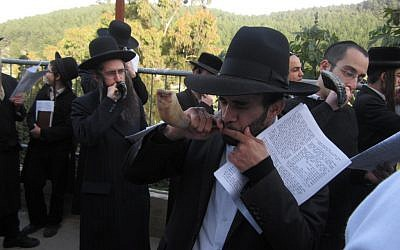 Unmarried men and their supporters blow shofars at the grave of Rabbi Yonatan ben Uziel near Safed. (Ben Sales/JTA)