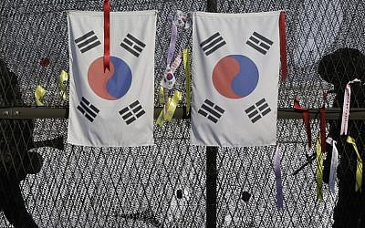 South Korean army soldiers patrol by the national flags and ribbons, wishing for the reunification of the two Koreas, attached on the barbed-wire fence at the Imjingak Pavilion near the border village of Panmunjom, which has separated the two Koreas since the Korean War, in Paju, north of Seoul, South Korea, Wednesday, Feb. 13, 2013 (photo credit: AP/Lee Jin-man)