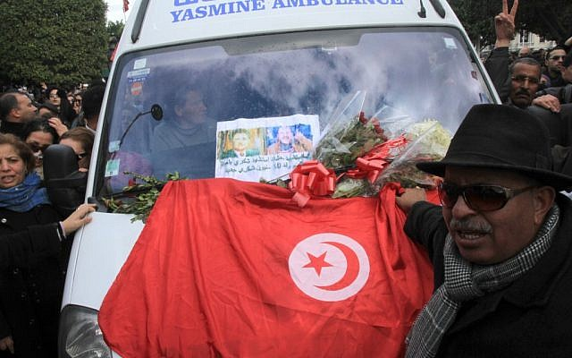Protesters gather with a Tunisian flag around an ambulance carrying the body of opposition leader Chokri Belaid in Tunis, Wednesday, Feb. 6 (photo credit: AP/Amine Landoulsi)