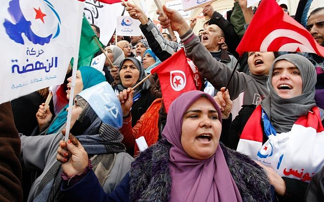 Supporter of the Islamist party Ennahda, hold Tunisian and party flags during a rally in Tunis, Tunisia on February 16, 2013. (photo credit: Amine Landouls/AP)