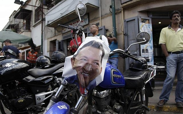 A poster of Venezuela's President Hugo Chavez decorates a motorbike near the military hospital where Chavez is allegedly receiving treatment in Caracas, Venezuela, on Wednesday (photo credit: AP/Ariana Cubillos)