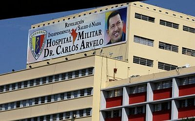 A banner bearing a photo of Venezuelan President Hugo Chavez is displayed on the military hospital where the ailing leader is continuing his recovery from surgery related to an unspecified cancer (photo credit: AP/Fernando Llano)