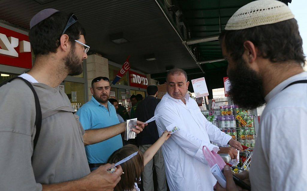 Members of Eretz Shalom movement giving candy to Arab shoppers as they mark the last Friday prayers of Ramadan, at the Rami Levy supermarket in Gush Etzion on August 17, 2012. (photo credit: Nati Shohat/Flash90)