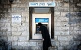 A man removes cash from a Bank Leumi ATM machine in the Meah Shearim neighborhood of Jerusalem (Nati Shohat/Flash90)