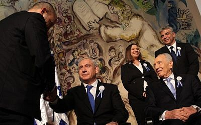 Prime Minister Benjamin Netanyahu, center, shakes hands with Jewish Home leader Naftali Bennett at the opening session of the Knesset earlier this month, as President Shimon Peres looks on. Behind them are Labor's Shelly Yachimovich and Yesh Atid's Yair Lapid. (Photo credit: Nati Shohat/Flash90)