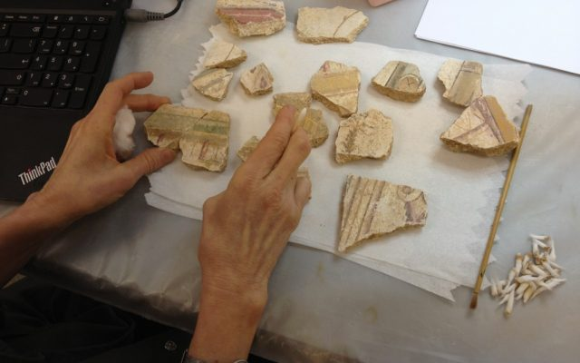 The hands of Connie Kestenbaum Green, piecing together the stucco trim from Herod's VIP room (photo credit: Jessica Steinberg/Times of Israel)