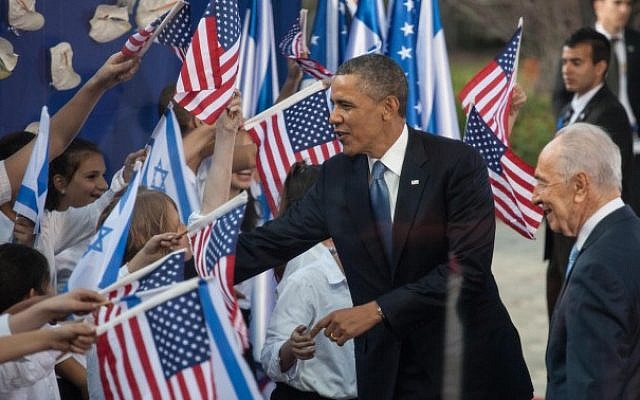 US President Barack Obama (left) and President Shimon Peres are greeted by children waving Israeli and American flags at a welcoming ceremony held for Obama in Jerusalem in March. (photo credit: Uri Lenz/Flash90)