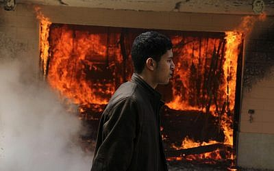 An Egyptian man walks on the grounds of a police officer's club as a fire set by protesters burns in Cairo, Egypt, Saturday, March 9, 2013 (photo credit: AP/Ahmed Gomaa)