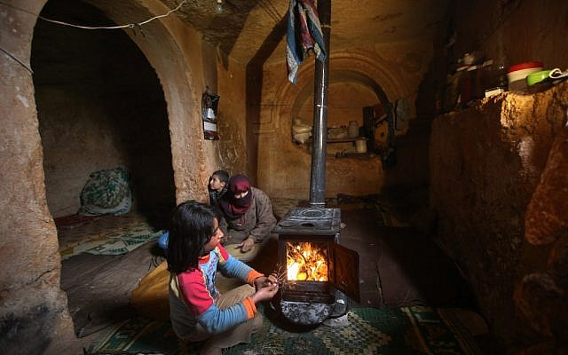 Nihal, 9, puts olive tree branches inside a wooden stove at an underground Roman tomb which his family uses for shelter from government shelling and airstrikes, at Jebel al-Zawiya, in Idlib province, Syria, on Thursday. (photo credit: AP/Hussein Malla)