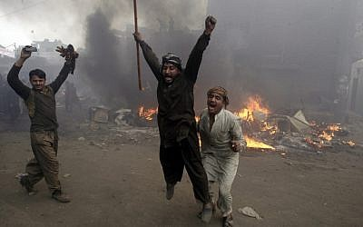 Pakistani men, part of an angry mob, react after burning belongings of Christian families, in Lahore, Pakistan, Saturday, March 9, 2013. (photo credit: AP/K.M. Chaudary)
