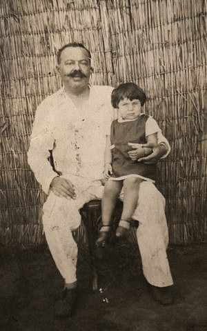 Avi Casuto sits on his father's lap in Cairo before their departure to Israel in 1956. (Courtesy of Ada Aharoni via JTA)