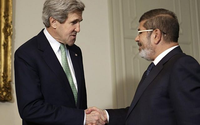 US Secretary of State John Kerry, left, shakes hands with Egyptian President Mohammed Morsi at the Presidential Palace in Cairo, Egypt, in March. (photo credit: AP/Jacquelyn Martin)