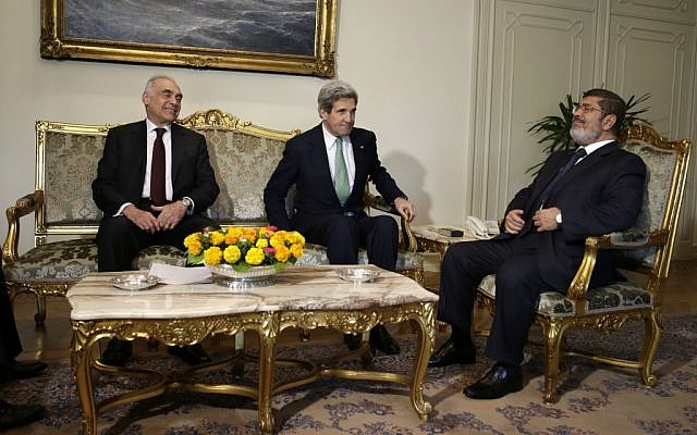 Egyptian Foreign Minister Mohammed Kamel Amr, left, U.S. Secretary of State John Kerry, center, and Egyptian President Mohamed Morsi take their seats at the starts of their meeting at the Presidential Palace in Cairo, Egypt on Sunday, March 3, 2013 (Photo credit: AP/Jacquelyn Martin, Pool).